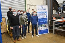 RealTide researchers waering face masks and standing socially distanced beside a RealTide poster